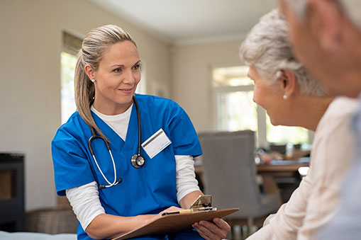 Blond Nurse With a Clip Board Listening to Elderly Patients