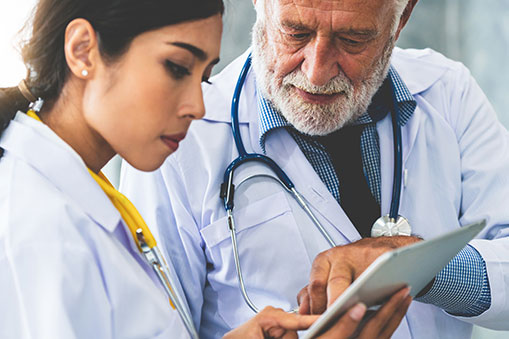 An Older Male Doctor Points Out Something on the Clipboard of a Younger Doctor